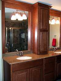 cherry cabinets and granite countertops in remodeled bathroom