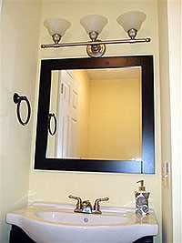 Black vanity mirror has matching cabinet.