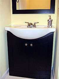 Black vanity cabinet matches mirror.