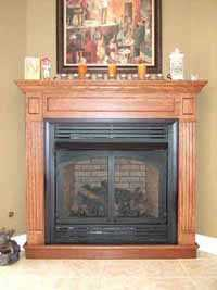 oak wood mantel and ventless fireplace surround in a basement